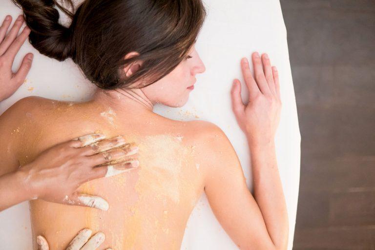 Una ragazza riceve un massaggio sulla schiena su un lettino bianco