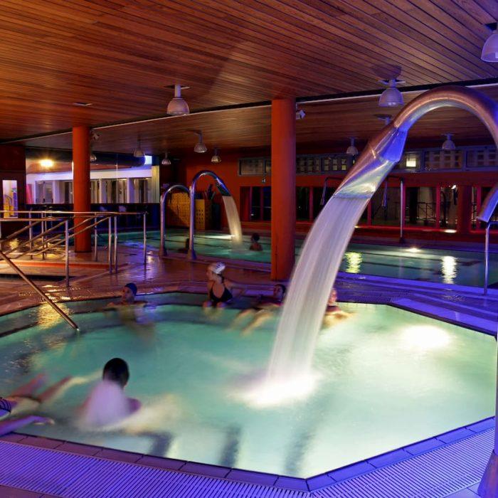 Vista delle piscine delle Terme della Salvarola. L'acqua esce da grandi docce cadendo dentro la piscina esagonale