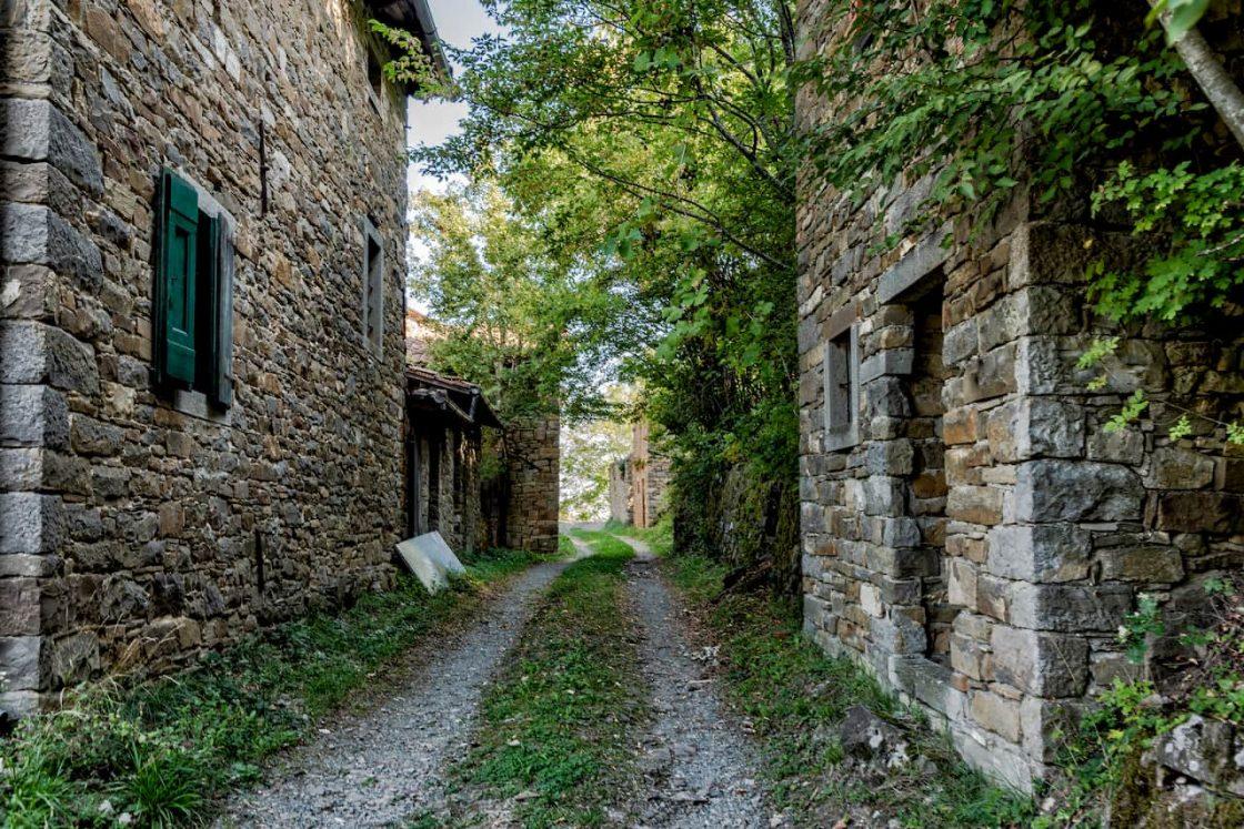 Una stradina bianca passa tra due costruzioni di pietra nel borgo di Palagano